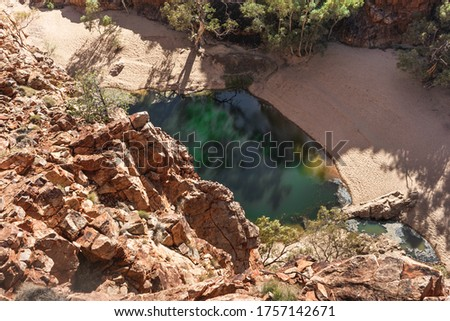 Water pond at Ormiston gorge pictured from above. Gorge with orange and red rocky walls. Vertical picture. Sun lighting from the side. Macdonnell ranges, Northern Territory NT, Australia, Oceania