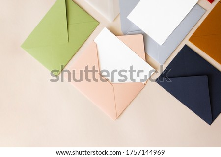 Close-up colorful mail envelopes on beige background flat lay with copy space, top view. Mailing concept isometric. White paper blank mockup for letters, greeting card, postcard, invitation Royalty-Free Stock Photo #1757144969