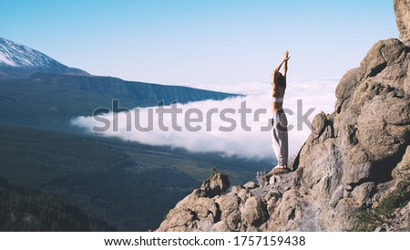 Woman enjoying nature. Female doing the yoga pose on background of natural landscape of mountains and sky. Mount Teide, volcano on Tenerife, Spain, Europe. Concept of vitality, zen energy, meditation. #1757159438
