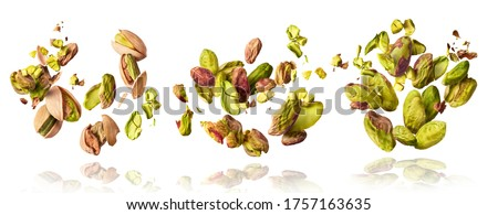A set with Flying in air fresh raw whole and cracked pistachios  isolated on white background. Concept of Pistachios is torn to pieces close-up. High resolution image #1757163635