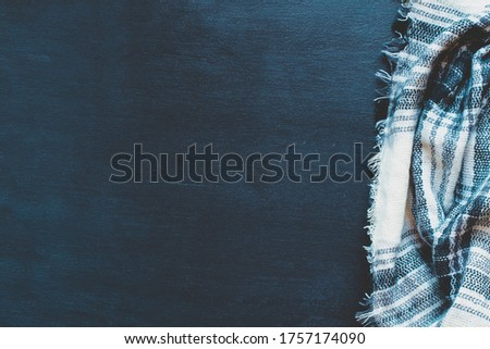Warm woven black, white and gray blanket crumpled over a black wooden background. Shot from above top view with free space for text for background.