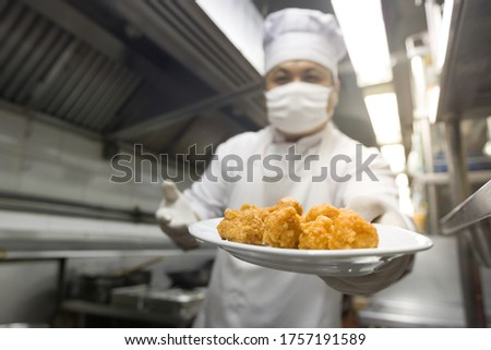 Chef holding plate of food for serving. chef joyful cooking in k #1757191589