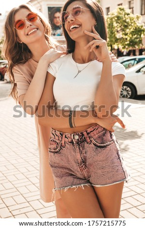 Two young beautiful smiling hipster girls in trendy summer clothes.Sexy carefree women posing on street background in sunglasses. Positive models having fun and hugging #1757215775