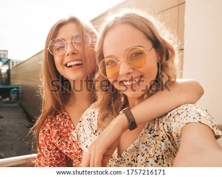 Two young beautiful smiling hipster girls in trendy summer sundress.Sexy carefree women posing on the street background in sunglasses. They taking selfie self portrait photos on smartphone at sunset