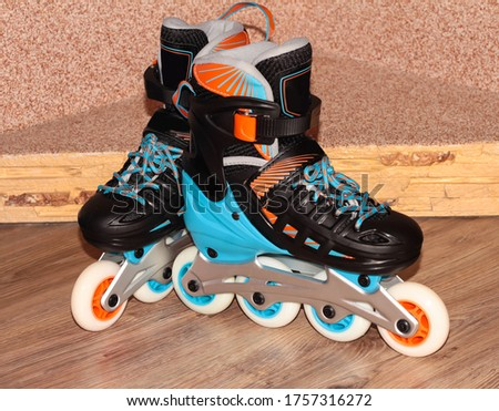 Roller skates on a wooden background. Roller skates are black and blue with orange color.