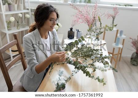 Smiling young Caucasian female florist design arrange bouquet on desk in studio, happy woman designer make floral composition for sale, compose flower house decorations, decor, gardening concept #1757361992