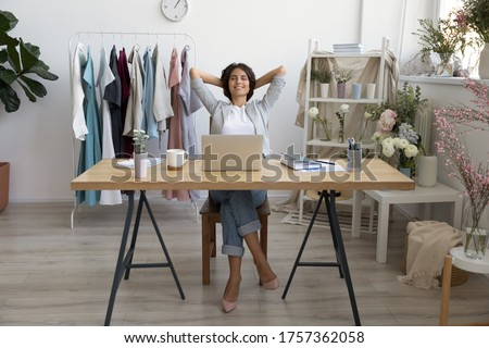 Relaxed young Caucasian female fashion designer or stylist rest in chair at desk daydreaming, happy businesswoman relax at workplace sleep or nap, relieve negative emotions, stress free concept #1757362058