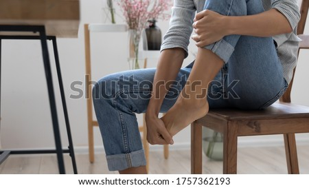Close up of exhausted businesswoman touch massage foot suffer from uncomfortable heels shoes at work, tired unwell female feel discomfort in legs, relieve pain from feet ache, have strained muscle #1757362193