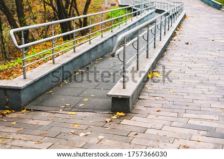 Ramp way for support wheelchair disabled people made from tiles with small fence and barriers. Public space in the park. Urban. Architecture. Free access. Mobility #1757366030