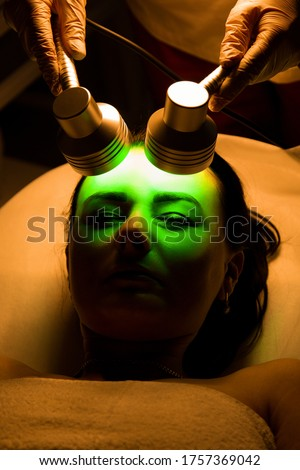 Color effect on the skin.Led Light Therapy.Chromotherapy procedure with Hydrafacial device.Woman doing LED face therapy in green #1757369042