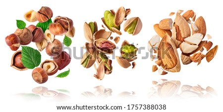 A set with Flying in air fresh raw whole and cracked pistachios, almonds and hazelnut isolated on white background. Concept of Pistachios almonds and hazelnut is torn to pieces close-up. #1757388038