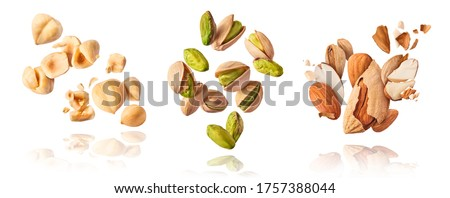 A set with Flying in air fresh raw whole and cracked pistachios, almonds and hazelnut isolated on white background. Concept of Pistachios almonds and hazelnut is torn to pieces close-up. #1757388044