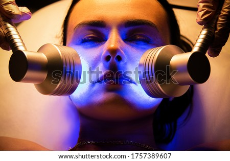 Led Light Therapy.Chromotherapy procedure with Hydrafacial device.Woman doing LED face therapy in blue  #1757389607