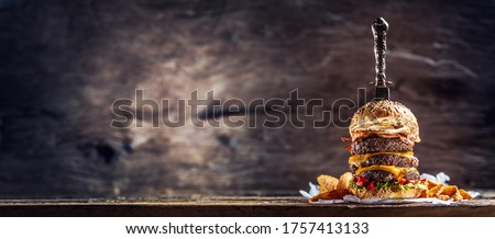Banner picture of knife stabbed in a triple cheeseburger with beef patty, melted cheese, egg and peppers in a rustic wooden environment.
