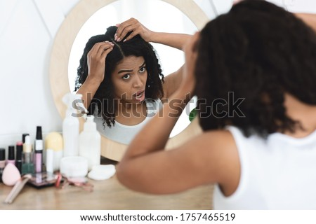 Dandruff Problem. Sad Black Woman Looking At Her Hair Roots With Flaky Scalp In Mirror, Sitting At Dressing Table, Over Shoulder View Royalty-Free Stock Photo #1757465519