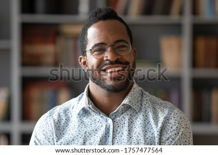 Head shot of african american bearded guy with pierced ear casual shirt smiling looking at camera standing indoor. Webcam view, conference video call, confident company representative portrait concept Royalty-Free Stock Photo #1757477564