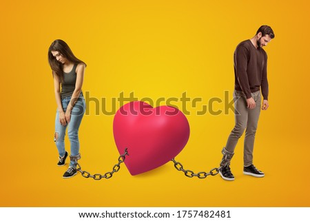 Young sad man and woman wearing casual clothes chained to pink heart on yellow background. Digital art. People and objects. Love problems.