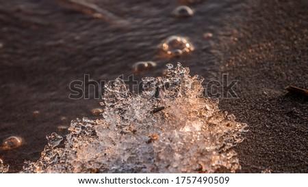 Ice on the sand of the beach #1757490509