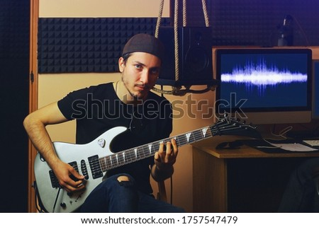 Young handsome creative man with a guitar in the darkness of a music studio, toned background #1757547479