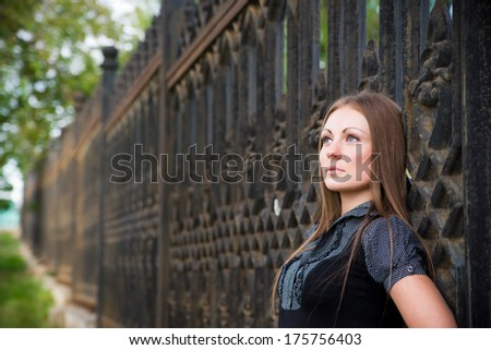 Beautiful young girl standing near fence. #175756403