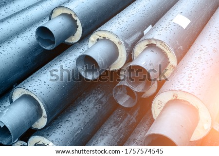 Heap of many new black insulated steel pipes at municipal construction site outdoors. Heating main district pipeline renewal or reconstruction. City development building industrial background Royalty-Free Stock Photo #1757574545