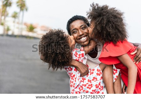 African sisters twins kissing mother on the beach - Black family having fun outdoor during summer vacation - Love, real people and travel concept - Main focus on mum face
