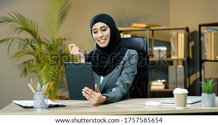 Beautiful Arab business woman using tablet for video conversation in modern office. Royalty-Free Stock Photo #1757585654