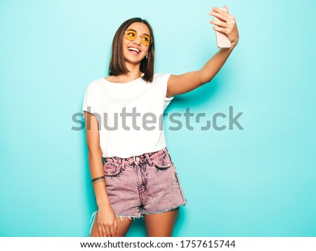 Beautiful smiling model dressed in summer hipster clothes.Sexy carefree girl posing in studio near blue wall in jeans shorts.Trendy and funny woman taking selfie self portrait photos on smartphone