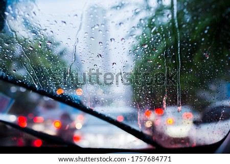 Selective focus to rain droplet with motion blurry wiper on windshield. Motion blurry windshield wipers from inside of car, season rain. Royalty-Free Stock Photo #1757684771