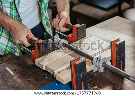 Bonding wood in the workshop. The use of glue for different types of wood. Making worktops for the kitchen. Work as a craftsman. Creating a cutting board design Royalty-Free Stock Photo #1757771960