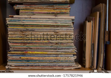 A stack of shabby old magazines and comics on a cabinet shelf. Collection of random magazines. Collecting, hobbies. Side view. Selective focus. Royalty-Free Stock Photo #1757821946
