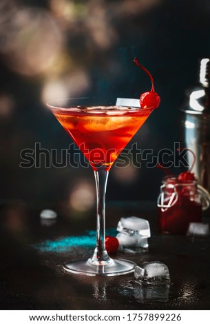 Manhattan alcoholic cocktail with bourbon, red vemuth, bitter, ice and cocktail cherry in glass, night mood image, copy space Royalty-Free Stock Photo #1757899226