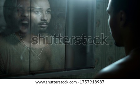 man in front of a mirror observing his deepest fears Royalty-Free Stock Photo #1757918987