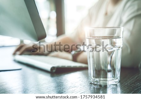 Drink clean room temperature water during working time for healthy and stay hydrated at work. Royalty-Free Stock Photo #1757934581