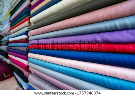 haberdasher fabric shop choice of textile material in fabric market. Shelves with colorful fabric rolls. clothes in shop, Rolls of fabric and textiles for sale stacked on shelves in shop. manifatura Royalty-Free Stock Photo #1757940374