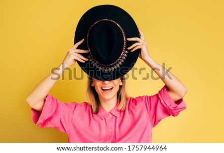 Picture of nice beautiful young woman cover upper face part with black hat. Girl hold tongue out of mouth. Young woman in pink shirt posing alone on camera. Isolated over yellow background #1757944964