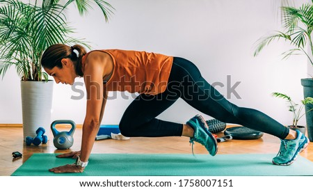 Mountain climbers, Woman Exercising Indoors, HIIT or high intensity interval training at home #1758007151