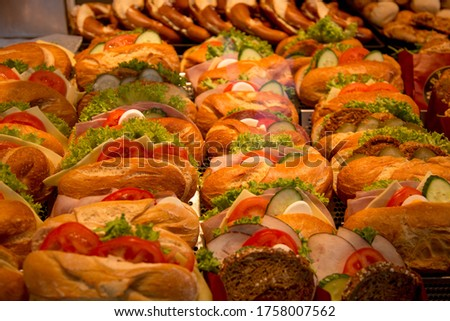 Assorted delicious baguette sandwiches filled with thinly sliced ham or salami and fresh green lettuce or basil arranged in an oblique row