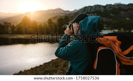 Senior man on hiking trip taking photographs of the view with a digital camera. Man hiker standing by the river in forest and taking photos.