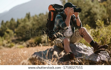 Senior man photographing with a digital camera. Retired man sitting on a rock and taking pictures on hiking trip.
