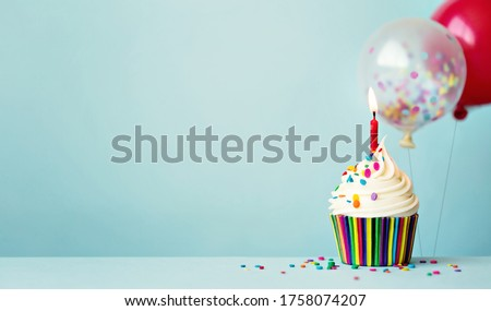 Birthday cupcake with colorful balloons and confetti Royalty-Free Stock Photo #1758074207