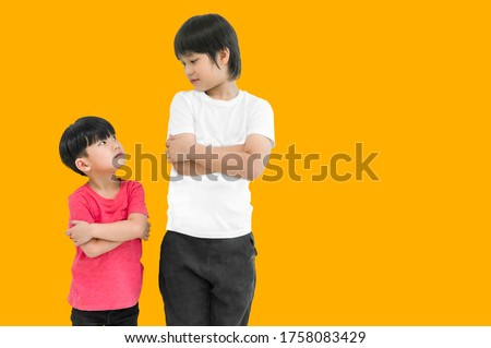 Little child boy and tall child boy standing arms crossed and looking face isolated on yellow background. Big and small kid concept at be friends. Back to school for concept. Royalty-Free Stock Photo #1758083429
