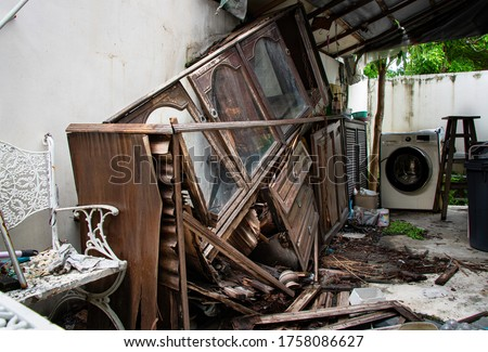 Hoarding disorder stay home in abandoned unorganized kitchen messy with broken ruined wooden old vintage antique cupboard collapse cabinets unhygienic glasses and dishes, dirty laundry washing machine #1758086627