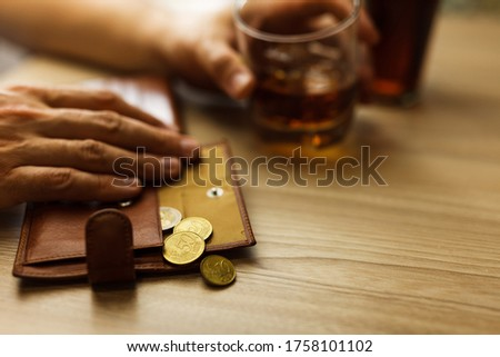 Fired man countsing his last money to drink expensive alcohol. Wrinkled alcoholic sits at brown wooden table with a glass of cognac with ice, on the table, empty wallet with coins Royalty-Free Stock Photo #1758101102