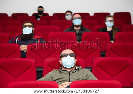 People in cinema with protection mask keeping distance away to avoid physical contact.Coronavirus COVID-19 disease protection.Social distancing practice #1758106727