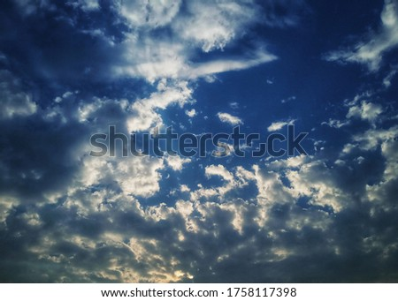 A beautiful picture of the sky. Surrounded by pleasing white clouds. Pic looks so natural and beautiful.  Also a little bit ray of the sun is shown in this picture.