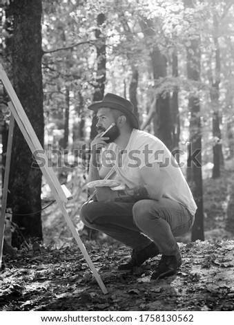 Man artist painting autumn picture. Autumn outdoor portrait of artist. He painting autumn picture