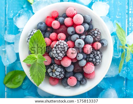 Frozen berry on turquoise  background top view Royalty-Free Stock Photo #175813337