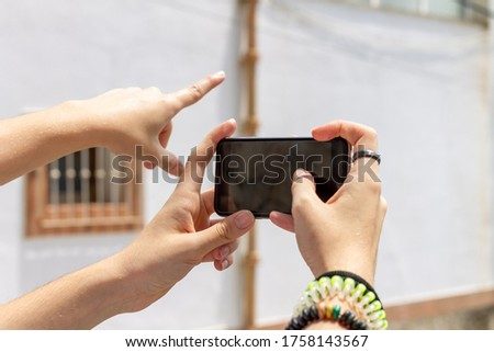 young girl with a friend's hand pointing at a picture on the street, concept of influence and use of social network.