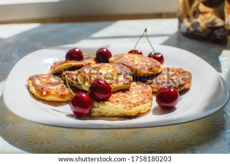 Curd cheesecakes on a white plate with red cherries Summer picture with summer associations. Inspiration for photographers. With space for text. Ideas for desserts and baking